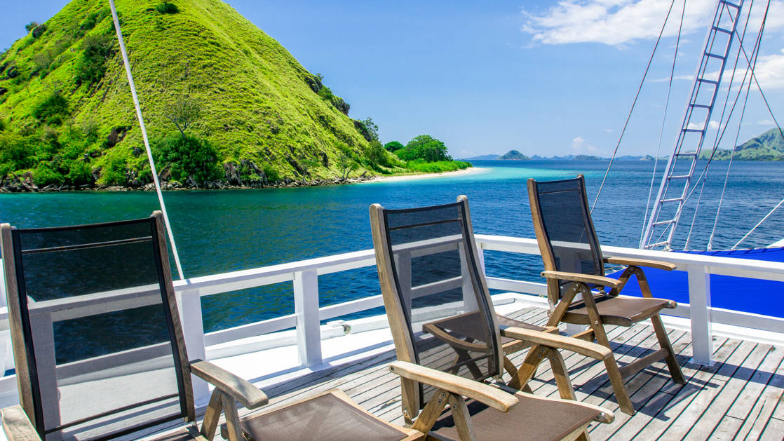 chairs on the deck of the ombak putih small ship with blue water and a green island in the background
