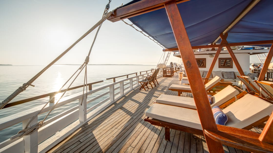 the deck of the ombak putih with a row of lounge chairs on a sunny day