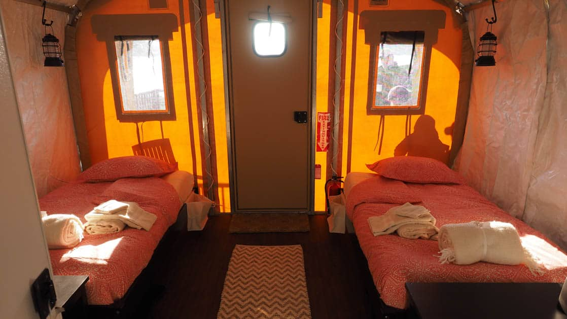 The interior of a private cabin with two twin beds at Base Camp Greenland in Sermilik Fjord