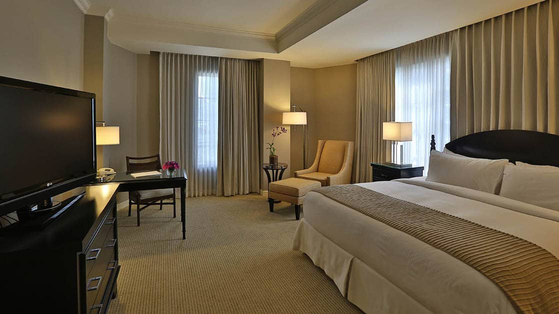 The deluxe room at the Panama Bristol Hotel with a king-sized bed, lounge chairs, and a flat-screen TV