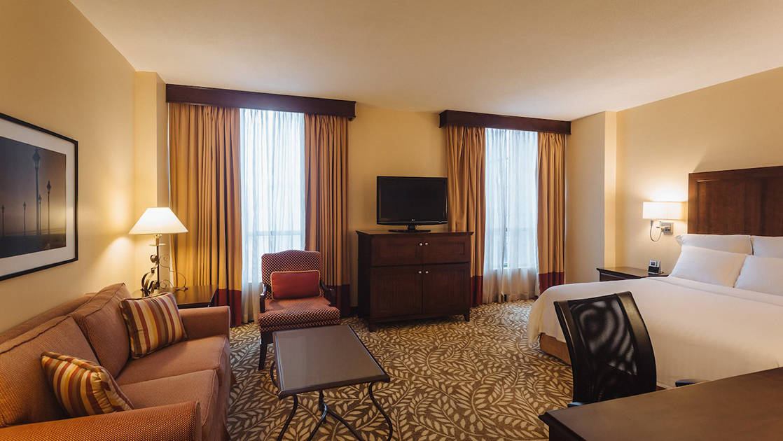 The executive guest room at the Marriott Hotel in Panama City features a king-sized bed, couch, table, reading lamps, television, and large windows.
