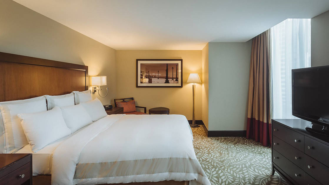 A king-sized bed with white linens, a television, and a private balcony at the Marriott Hotel in Panama City.