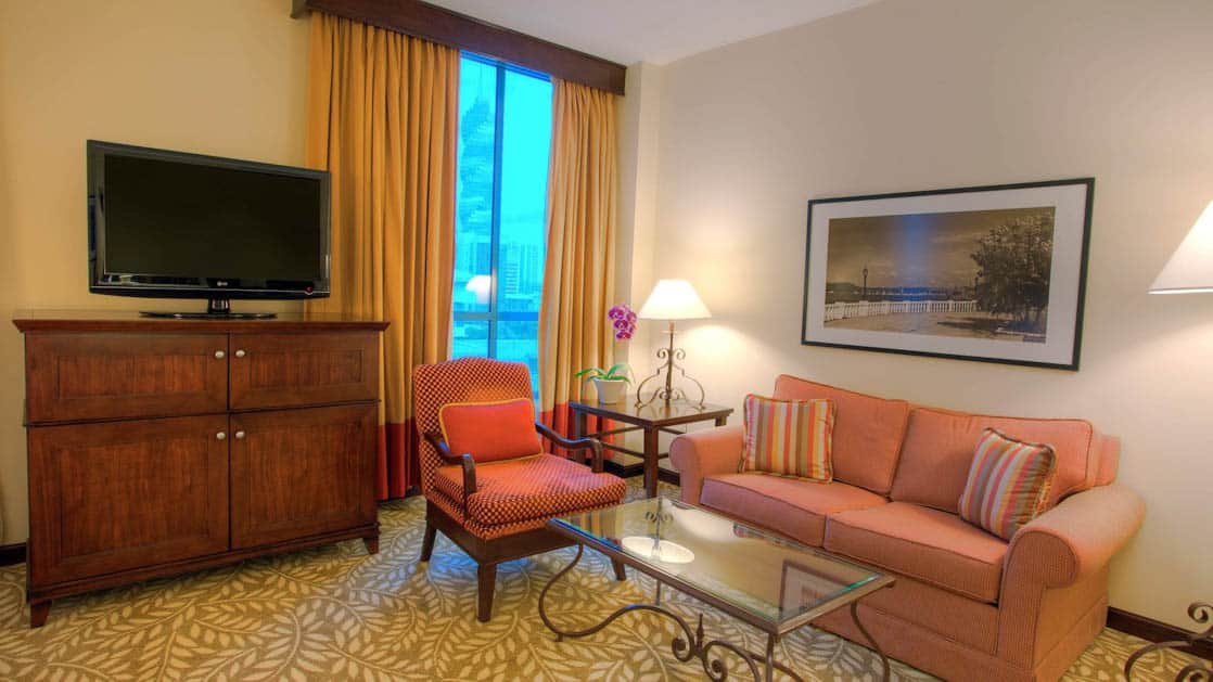 A couch, sitting chair, coffee table, television, and large window inside the premium deluxe room at the Panama Marriott Hotel.