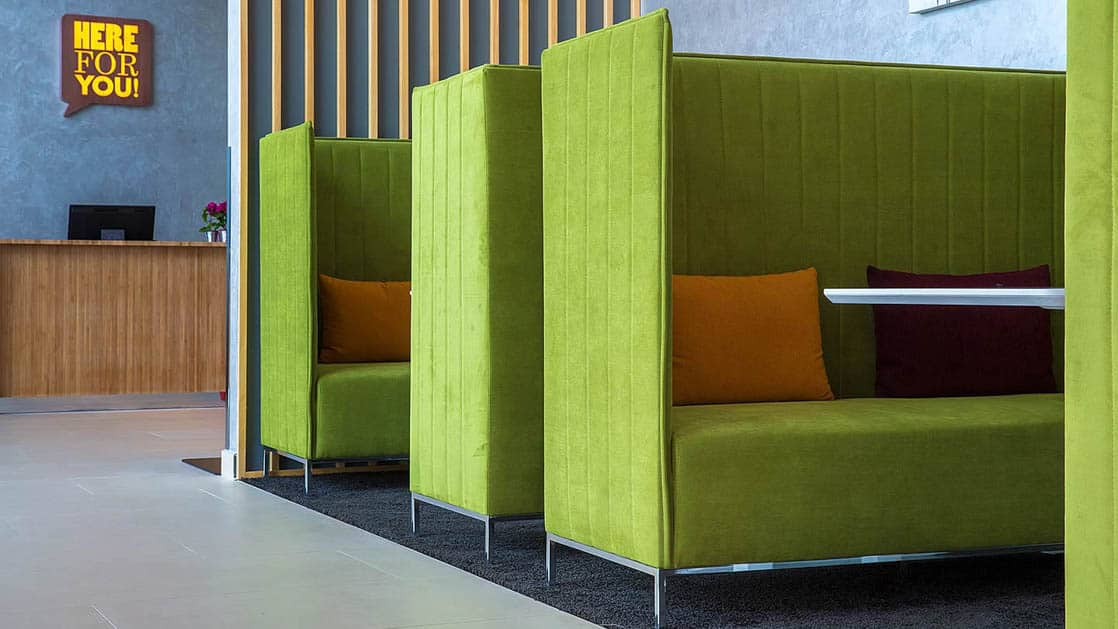 Green booths line a wall in the reception area at the Park Inn by Radisson, located in San Jose, Costa Rica