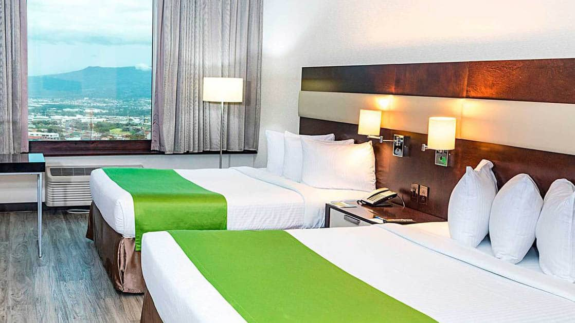 A window with a view of San Jose, Costa Rica, and two beds with white linens and a green duvet inside the standard double room at the park inn by radisson.