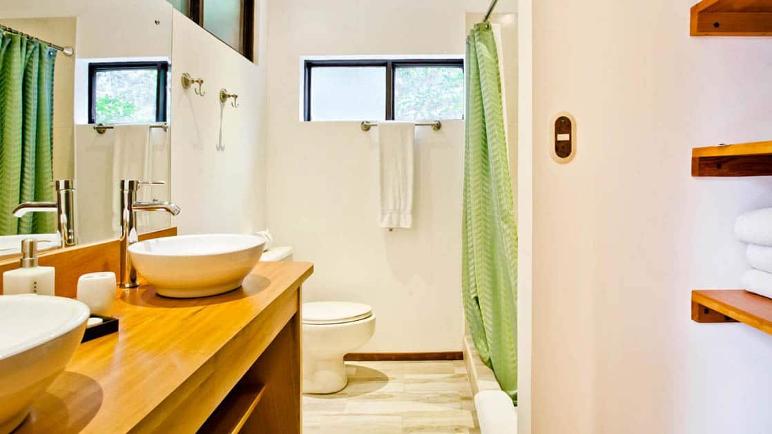 The bathroom inside the forest view balcony room has two sinks, a vanity, bathroom, and solar-heated hot showers at the Monteverde Lodge, a sustainable, nature retreat on the edge of a well-known cloud forest in Costa Rica
