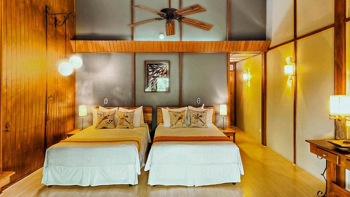 Two twin beds in a forest room with a ceiling fan and wood beams at the Monteverde Lodge, a sustainable, nature retreat on the edge of a well-known cloud forest in Costa Rica