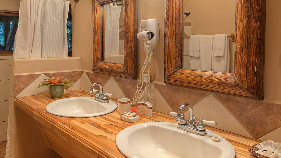 Two sinks on the vanity with a mirror in the private bathroom at the river view penthouse suite at Tortuga Lodge, a luxury eco resort in Costa Rica