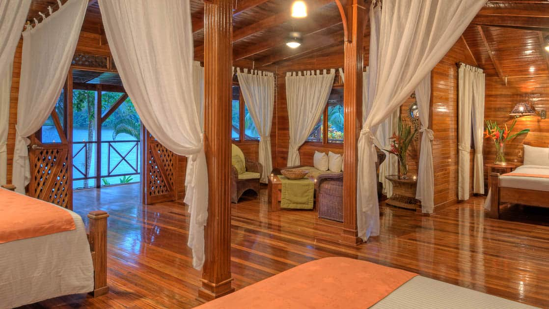The River View Penthouse Suite with one king and one queen Bed closed off by gauze curtains, at the Tortuga Lodge, one of Costa Rica's most environmentally conscious accommodations.