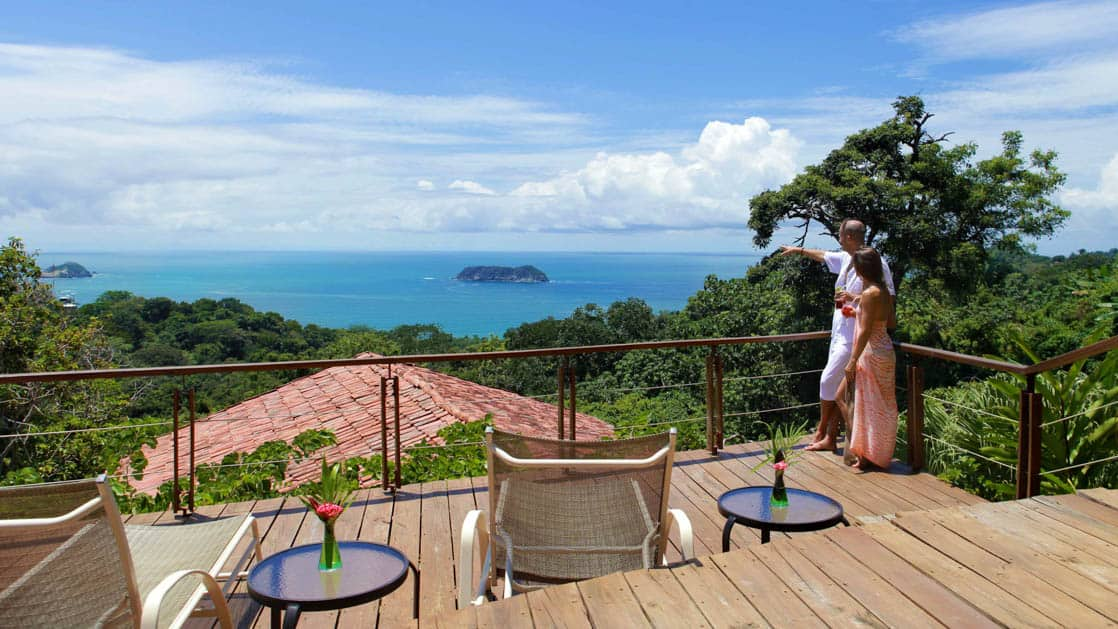 A deck with lounge chairs and small tables overlooks the red tiled roofs at Si Como No, a boutique resort, and the Pacific Coastline in Costa Rica