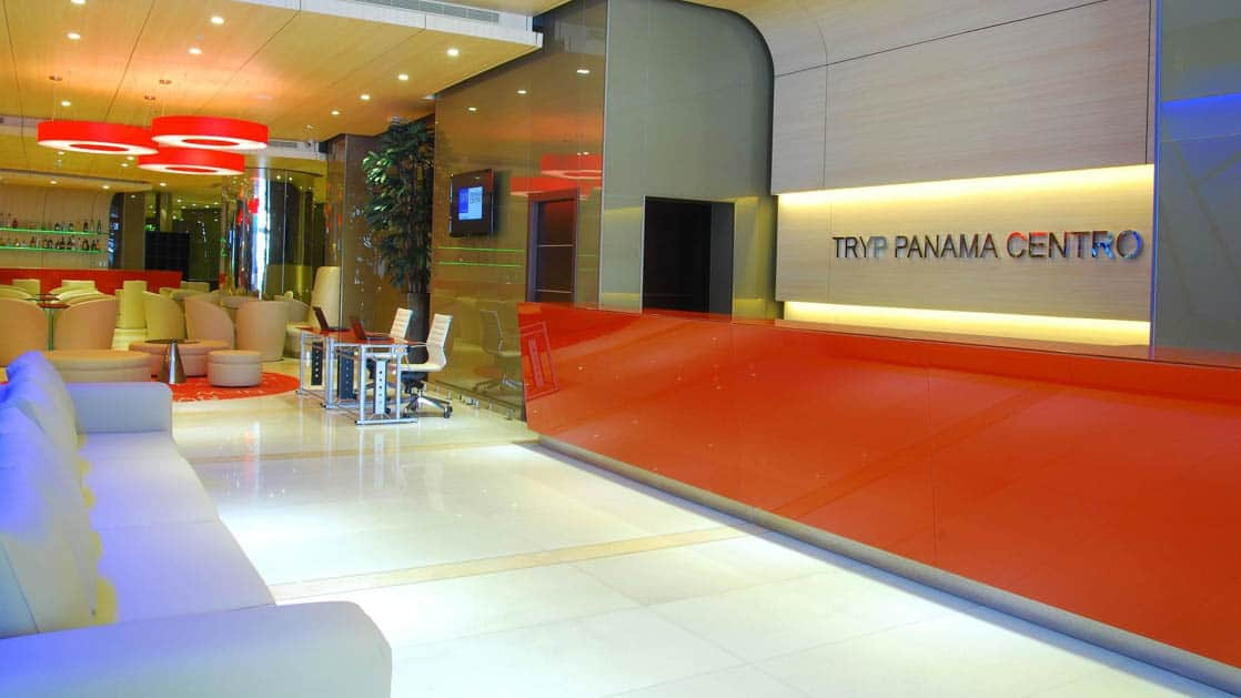 The reception desk in the contemporary lobby with seating, at the Hotel Tryp by Wyndham Panama Centro