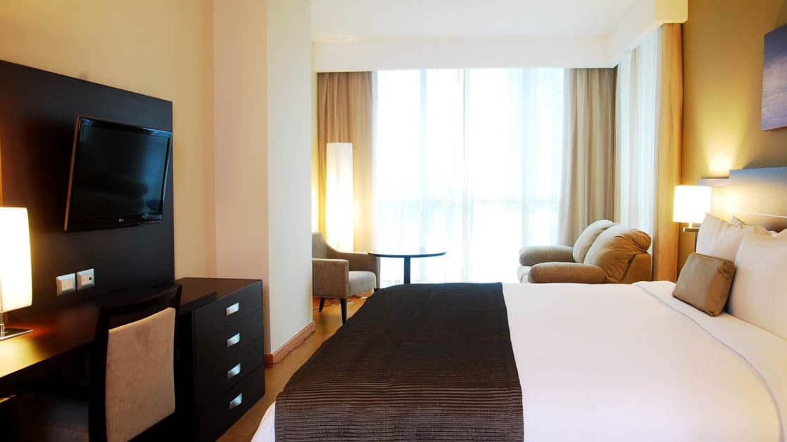 A room with a king-sized bed, television, chairs, and a large window at the Hotel Tryp by Wyndham Panama Centro