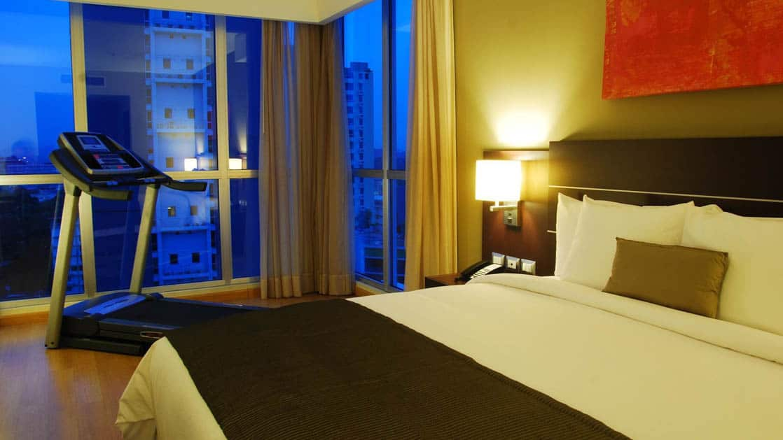 At dusk, a room with a queen-sized bed and a treadmill at the Hotel Tryp by Wyndham Panama Centro
