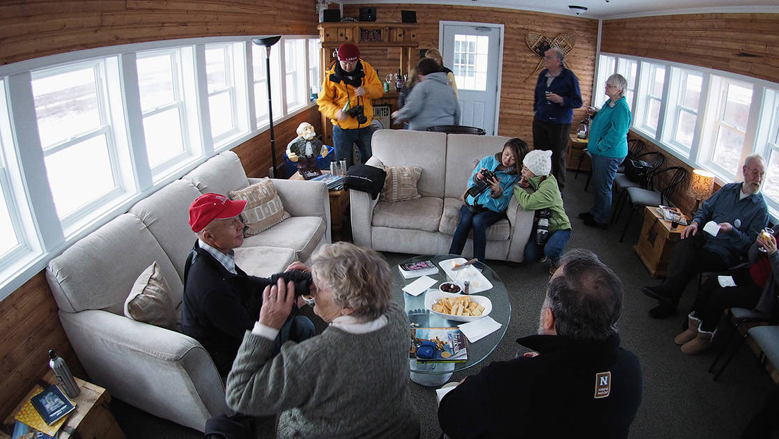 Guests sit on couches in a common area and look at pictures they just took on their cameras at the Tundra Lodge, a unique, rolling hotel, located in the subarctic outside the small Canadian frontier town of Churchill, Manitoba