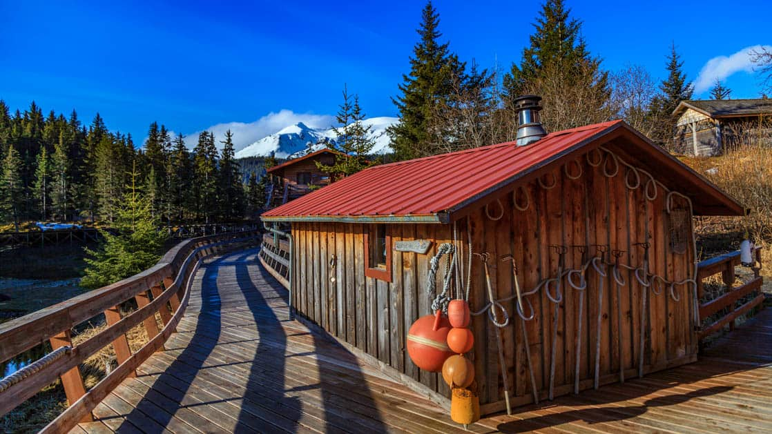 The sauna is located inside a wood cabin with a red roof, next to a boardwalk, with snow-capped mountains and pine trees in the distance, at the Tutka Bay Wilderness Lodge in Alaska