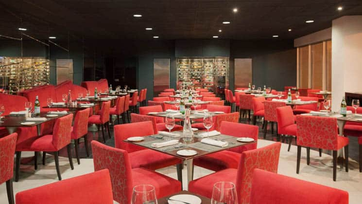 Plush red chairs are positioned around tables set for fine dining at the restaurant inside Wyndham Costa del Sol hotel, connected to the Lima International Airport