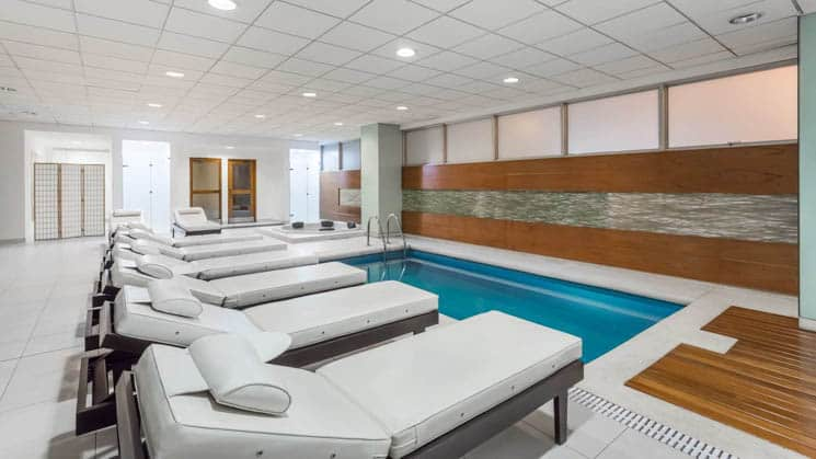 White lounge chairs are in a row next to the indoor pool at Wyndham Costa del Sol hotel, connected to the Lima International Airport
