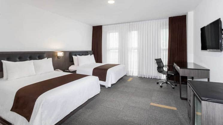 A suite with two queen-size beds, television, dresser, and large windows at the Wyndham Costa del Sol hotel, connected to the Lima International Airport