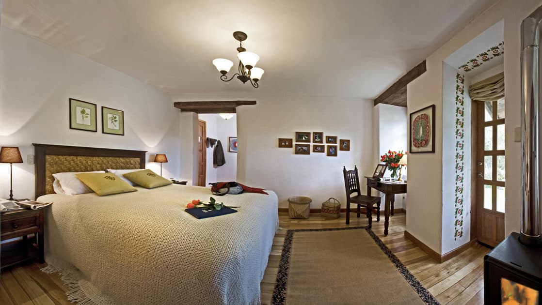 Room interior with bed, bedside tables, desk and chair at Hacienda Zuleta in Ecuador