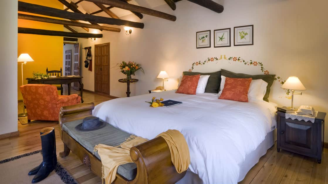 Room interior with bed, bench, armchair, desk and chair at Hacienda Zuleta in Ecuador