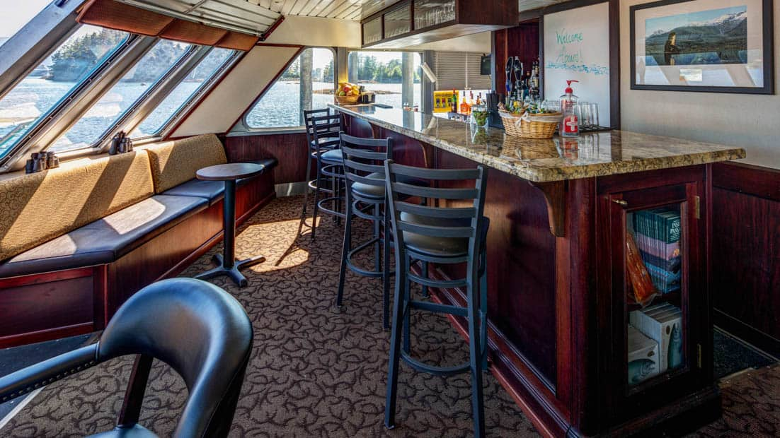 Bar with stools and benches by window aboard Alaskan Dream.