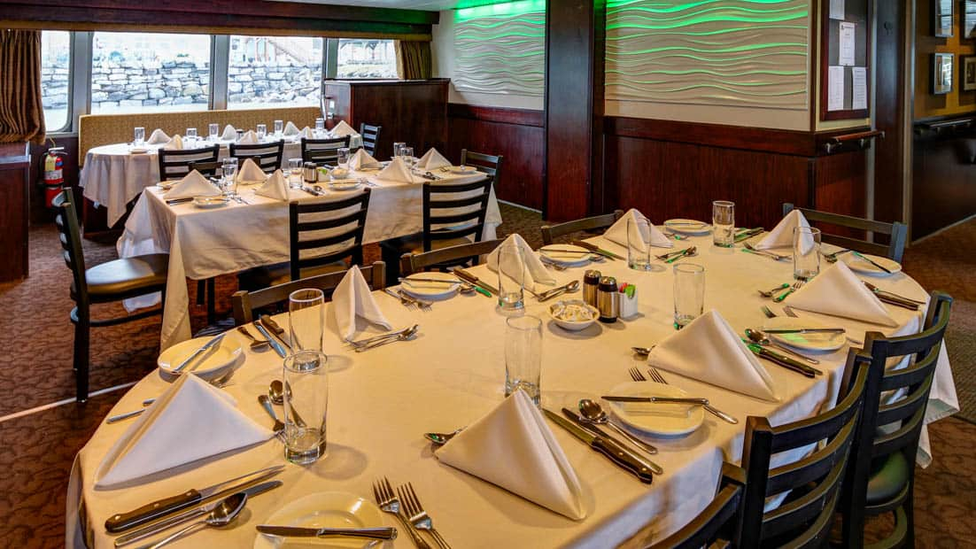 Three set tables in the dining room aboard Alaskan Dream.