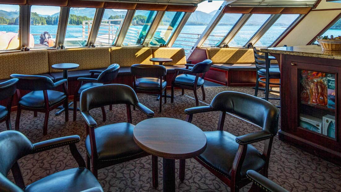 Lounge area with many chairs and tables aboard Alaskan Dream.