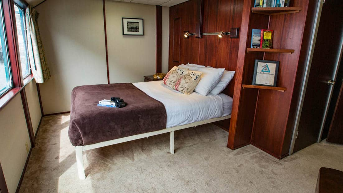 Owner's Suite aboard Alaskan Dream with large bed and window.