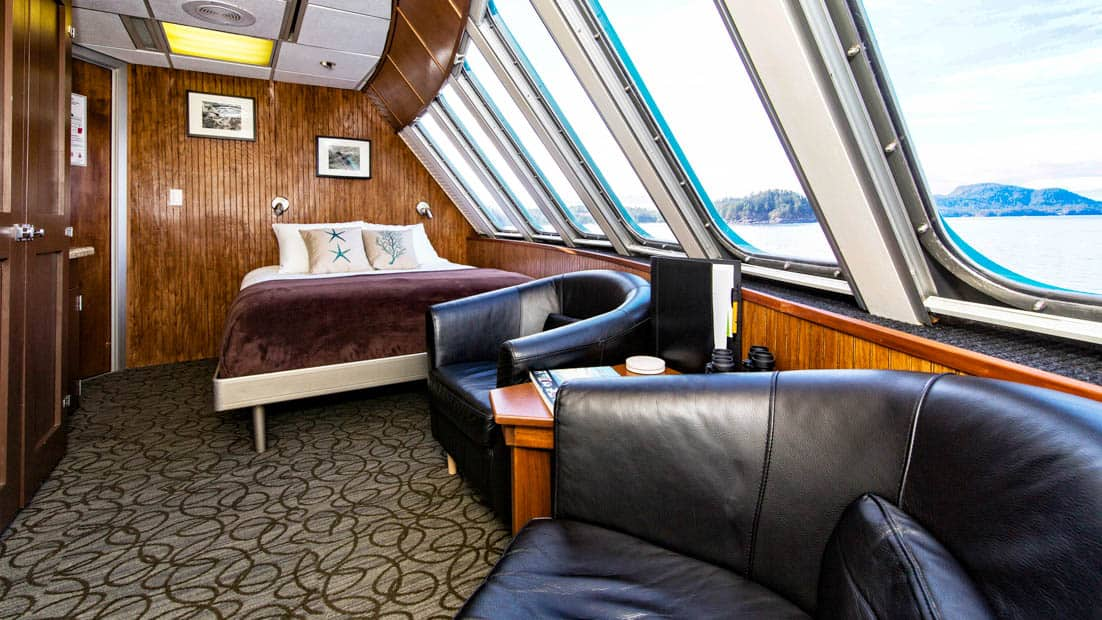 Vista View suite aboard Alaskan Dream with two leather chairs, bed, and many windows.