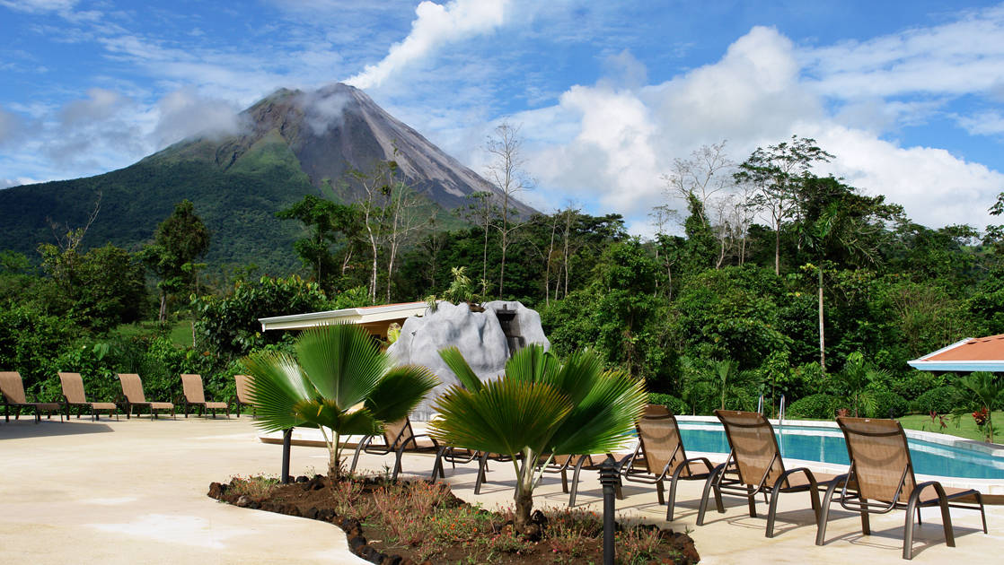 Costa Rica's Arenal Volcano rises behind a jungle forest, with the hotel's pristine pool, lounge chairs, and an umbrella in the foreground.
