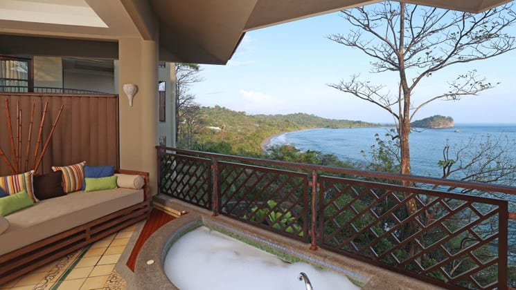 A hot tub on a balcony with an ocean view at Arenas Del Mar in Costa Rica