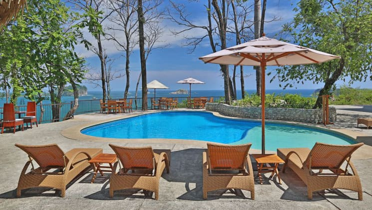 The pool and lounge chairs at Arenas Del Mar, a luxury lodge in Costa Rica.