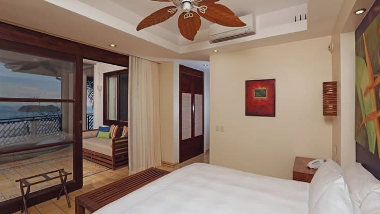 An oceanfront room with a large bed and a balcony Arenas Del Mar resort in Costa Rica.