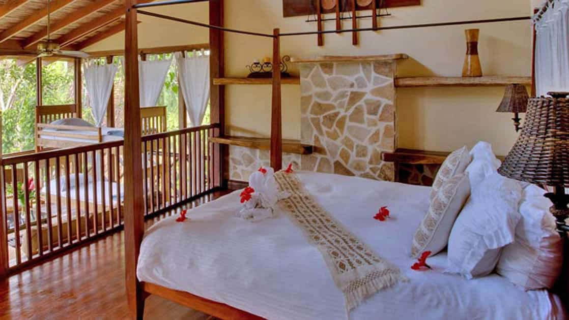 Master bedroom loft with large bed and twin bunk beds surrounded by lush forest at Caves Branch Jungle Lodge in Belize