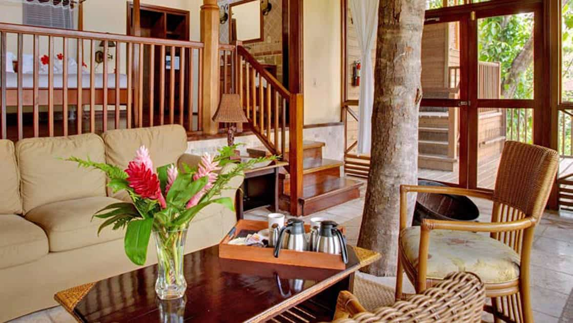 Fresh flowers and coffee on a small table surrounded by couches and chairs with a live tree growing in living room space of Caves Branch Jungle Lodge in Belize