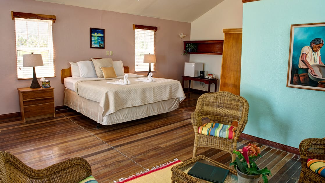 One of the deluxe cabanas at the Blackbird Caye Resort in Belize with one queen bed, a wicker chair, colorful accents.