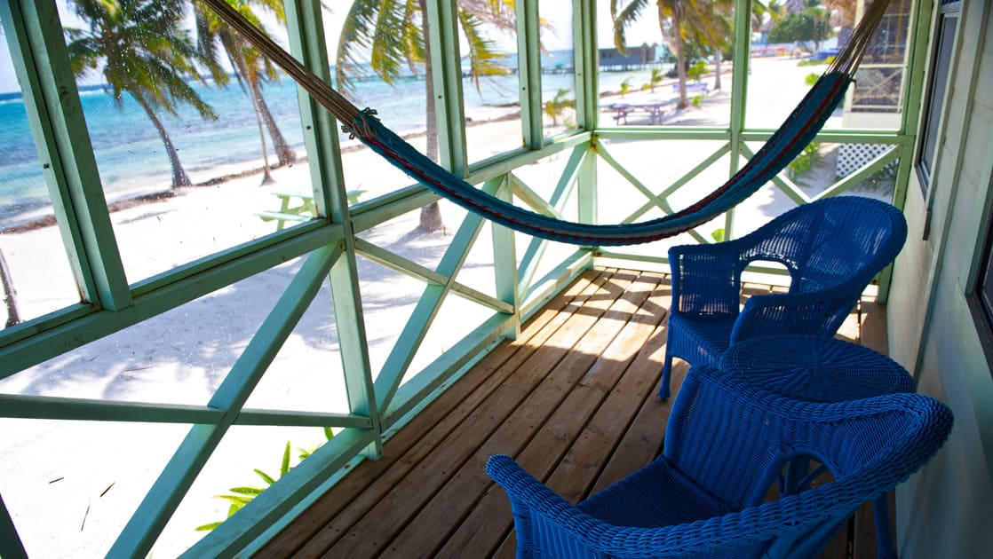 A blue hammock and two chairs are situated on a shady porch, just off the beach with palm trees and the Caribbean water.