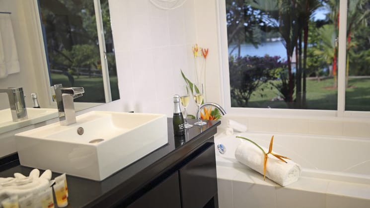 A contemporary bathroom with fresh flowers and white linens at the Bocas del Mar hotel in Panama