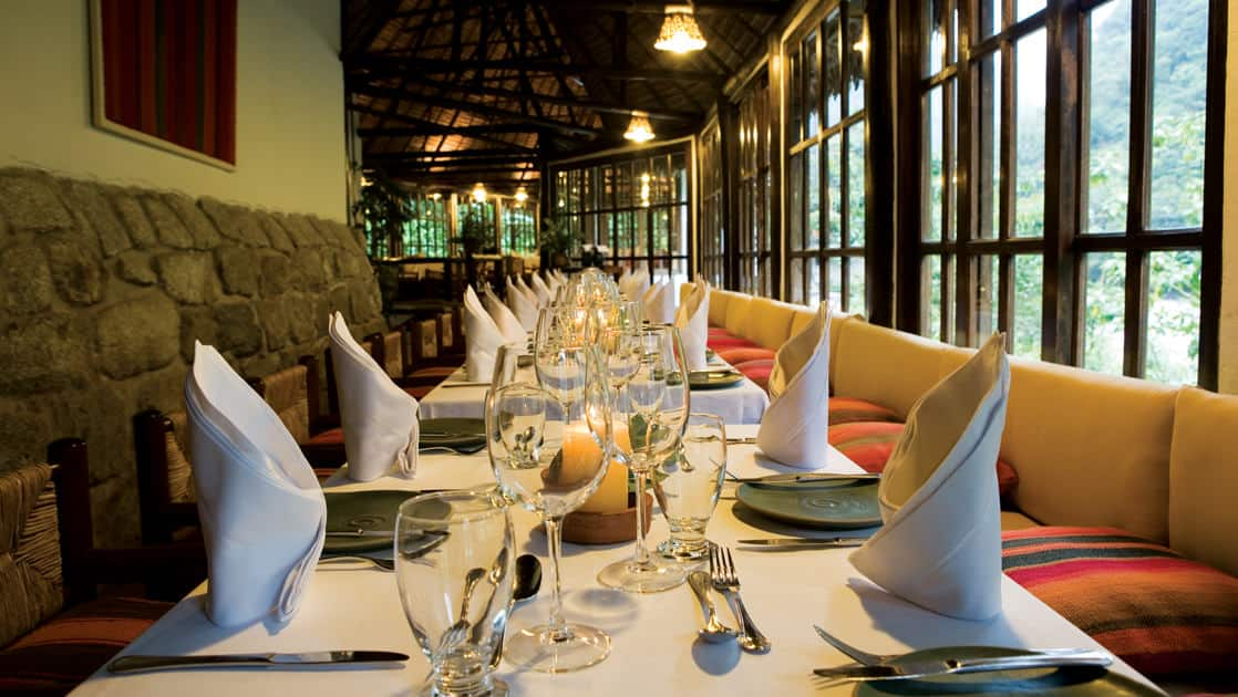 A long table is set with white tablecloths and napkins and fine dining silverware at Café Inkaterra, a restaurant that blends Andean cuisine and architecture with a contemporary approach, creating innovative fusion-style fare.