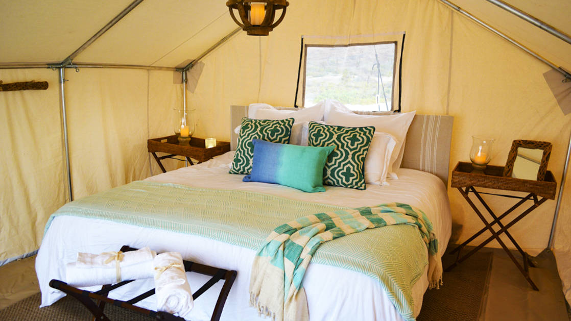 A queen-sized bed with blue accent pillows, bedside tables, and fresh linens in one of the glamping tents at Camp Cecil, a beachfront abode on an island in Baja