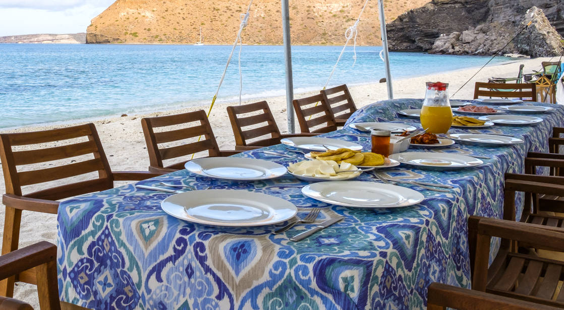 A long table is set with a blue print tablecloth, plates, and chairs for beachside dining at Camp Cecil, where Espiritu Xantus Café is where fresh, healthy meals are prepared by the on-site chef.