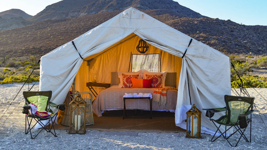 One of the luxury, beachfront, glamping tents at Camp Cecil, located on Espiritu Santo Island in southern Baja, with a queen-sized bed, camping chairs, lanterns, and comfortable bedding.