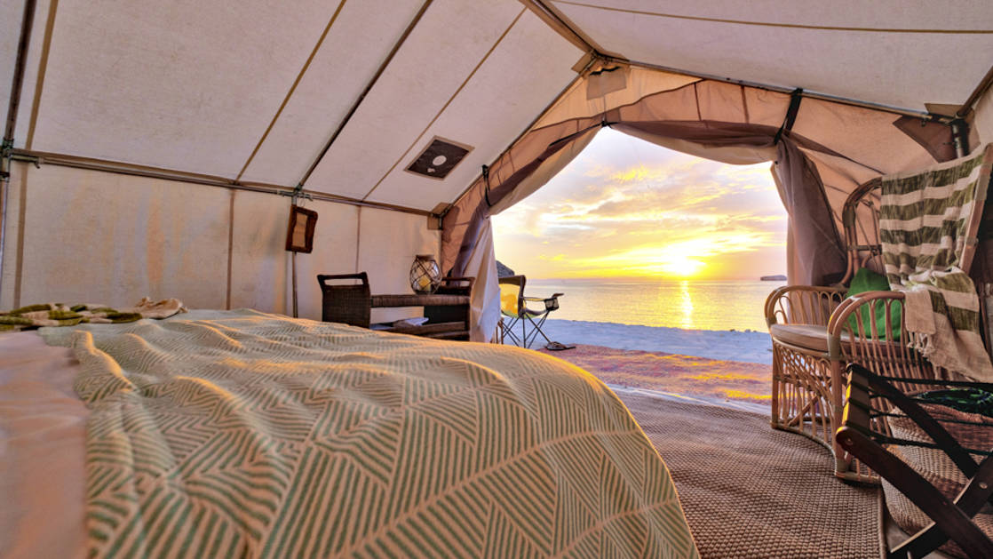 Shades of pink illuminate the sky during a sunset outside the private, comfortable tent at the beachfront Camp Cecil in Baja, Mexico