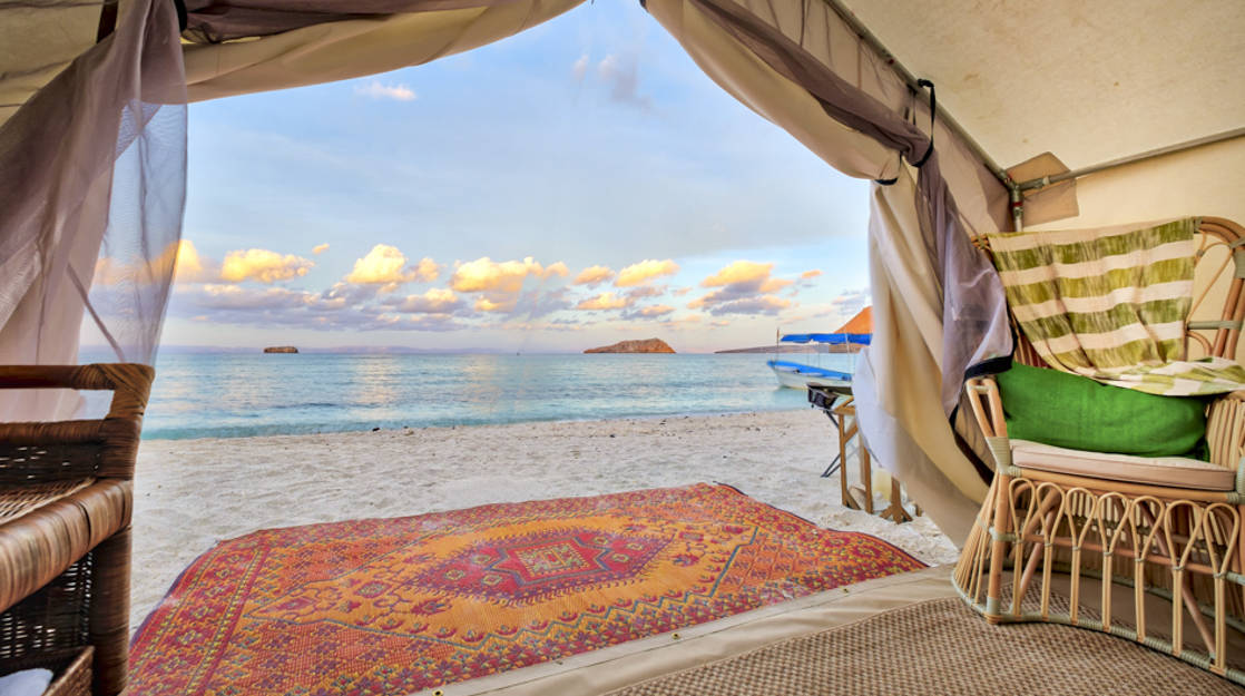 A red rug is set just outside the glamping tent on the sand, with a view of the Sea of Cortez, at Camp Cecil, in Baja Mexico