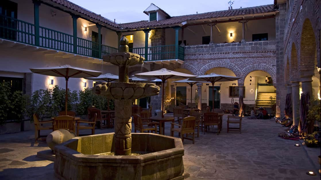 The fountain in the courtyard at Casa Andina Premium in Cusco, Peru, with an arched walkway and two story hotel for guests to relax.