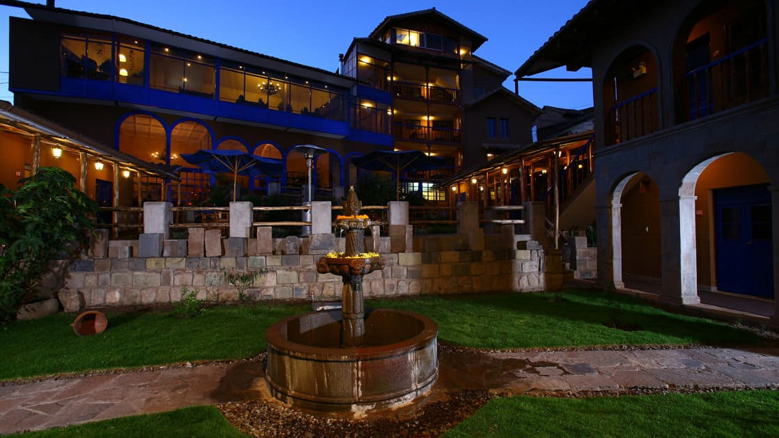 Night sets in with a view of the fountain, lawn, and courtyard at Casa Andina Premium, a hotel in Cusco, Peru.