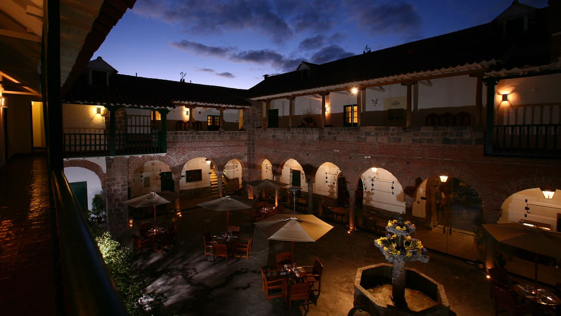 Lights are flickering in the courtyard at Casa Andina Premium in Cusco, Peru, which feels like a rustic Andean home with arches and fountains.