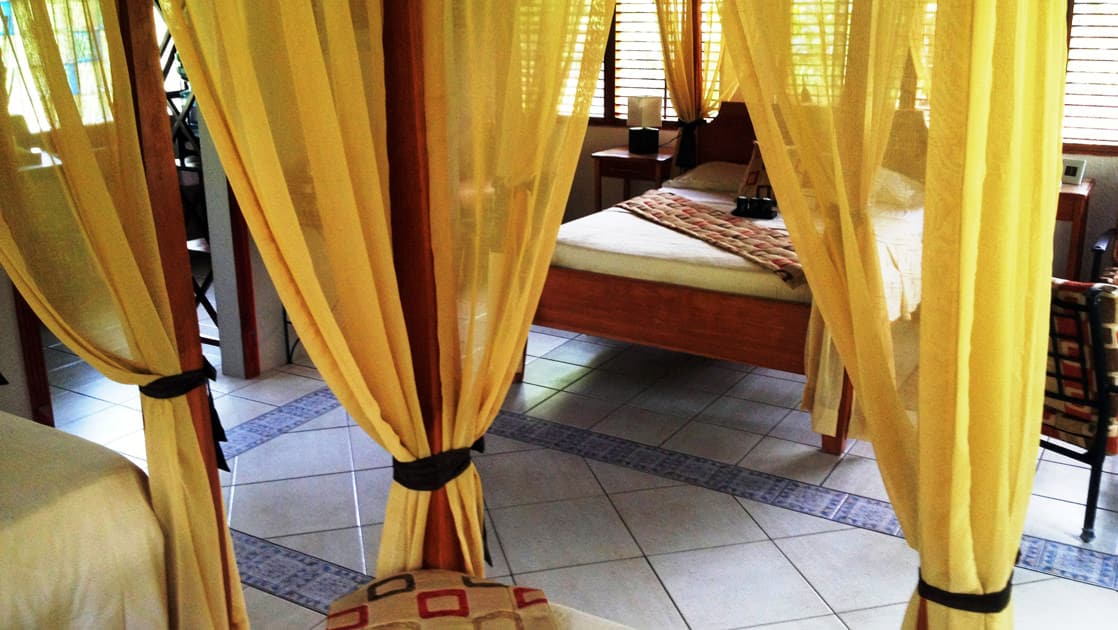 Four-post bed with yellow curtains and tile floor in a deluxe bungalow at Casa Corcovado Jungle Lodge in Costa Rica