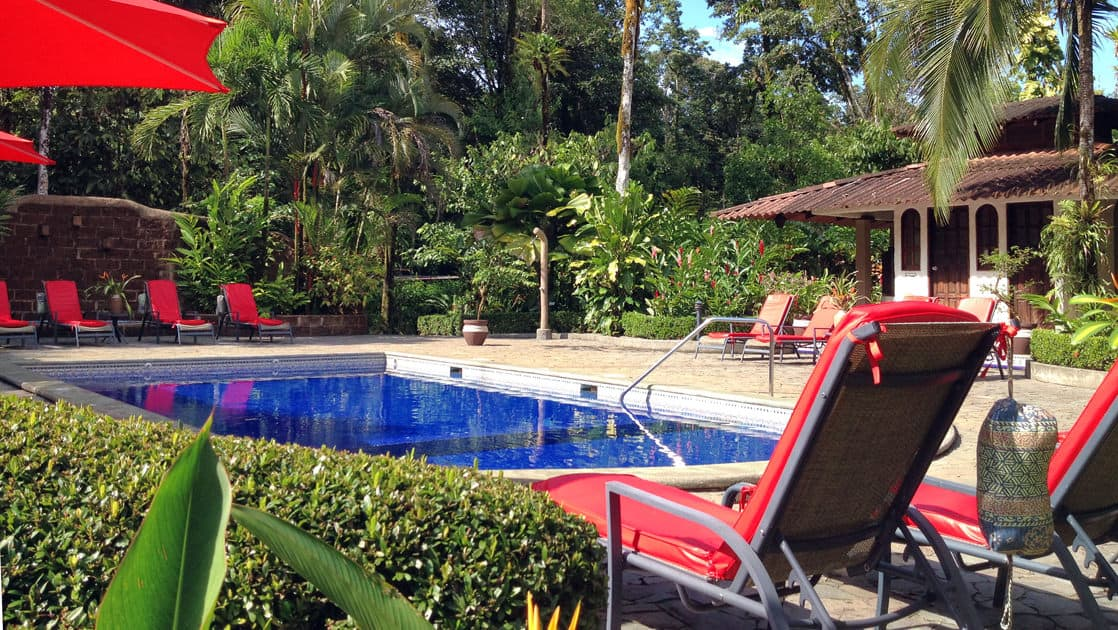 Large pool with lounge chairs and shady umbrellas at Casa Corcovado Jungle Lodge in Costa Rica