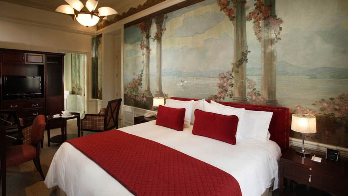 A hand-painted fresco with flowers and pillars behind huge bed with nearby sitting area in a Luxury Plus room at Casa Gangotena in Quito, Ecuador